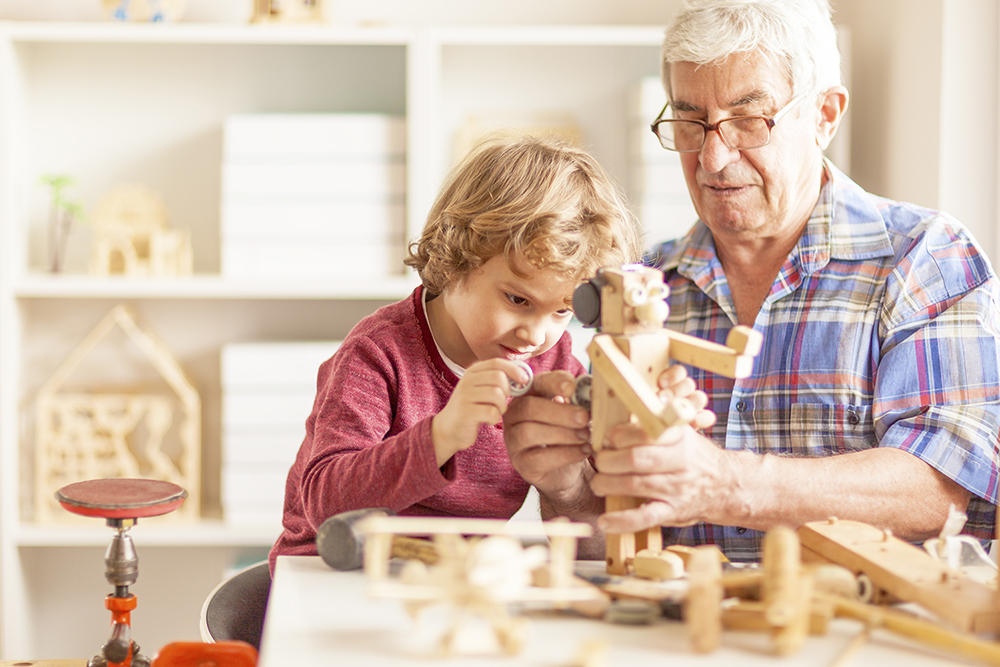 Grandpa and his grandson crafting wooden toys together in a workshop